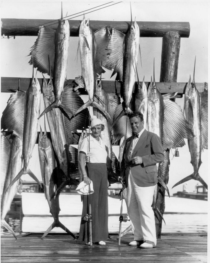 man and woman with hanging sailfish